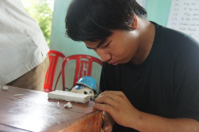 Hình 15: Sơn, một thanh niên địa phương, tham gia làm mô hình với nhóm thiết kế.
