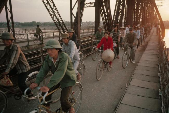 Sau một ngày làm việc, người lao động trở về nhà trên cầu Long Biên (Hà Nội), cây cầu từng bị bom đạn Mỹ phá hủy trong thời chiến tranh.