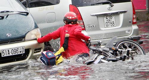 Một người mẹ đang chống chọi giữa dòng nước với đứa con nhỏ bám chặt lấy mẹ ở phía sau để khỏi rơi xuống nước. Ảnh: An Nhơn, Vnexpress